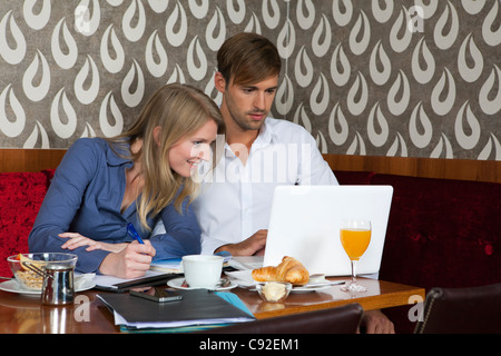 Couple studying with laptop in cafe - Stock Photo