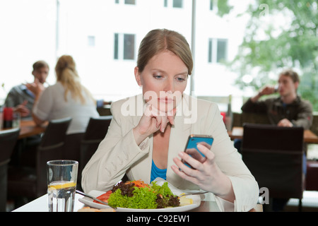 Businesswoman using cell phone at lunch - Stock Photo