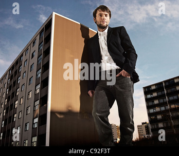 Oversized man leaning on building - Stock Photo