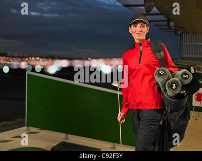 Woman with golf clubs at driving range - Stock Photo