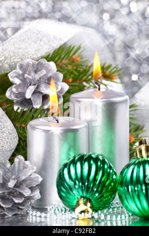 Christmas balls with silver candles over bright background - Stock Photo