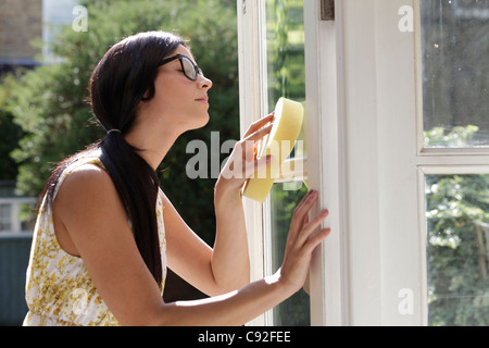 Woman carefully cleaning glass doors - Stock Photo