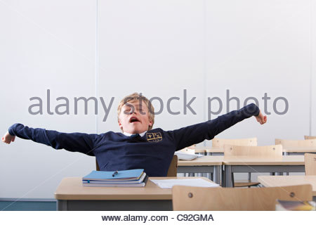 Male student in school uniform yawning and stretching at desk in classroom - Stock Photo