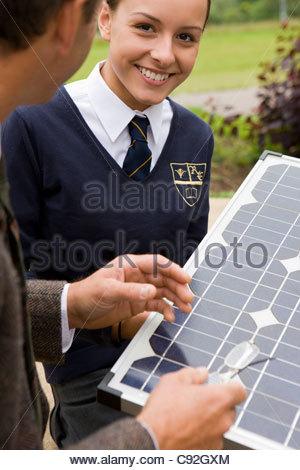 Portrait of smiling female student holding solar panel with teacher - Stock Photo