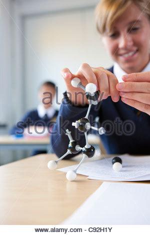 Female student in school uniform assembling atom model on desk in classroom - Stock Photo