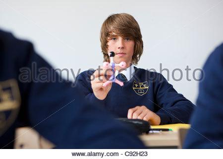 Portrait of male student in school uniform holding atom model at desk in classroom - Stock Photo
