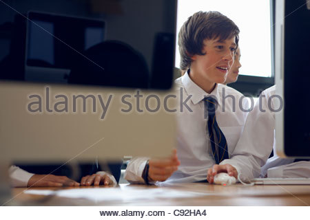 Students in school uniform using computers - Stock Photo