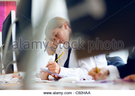 Female student in school uniform writing in notebook at computer - Stock Photo