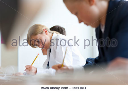 Students in school uniforms taking exam at desks in classroom - Stock Photo