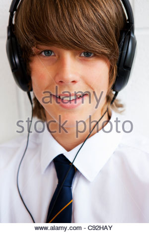 Close up portrait of smiling male student in school uniform wearing headphones - Stock Photo