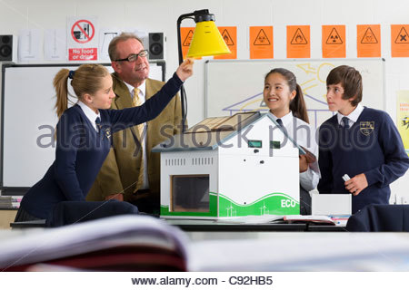Teacher and students in school uniforms adjusting lamp over solar panels on house model in science class - Stock Photo