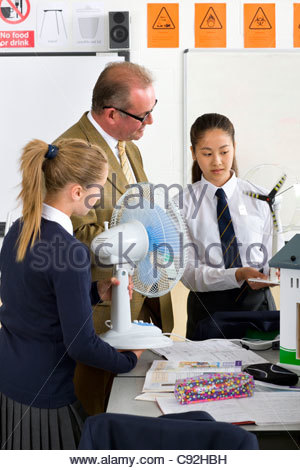 Teacher and students in school uniforms with wind turbine model in science class - Stock Photo