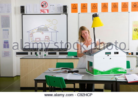 Female teacher adjusting solar panels on house model in science class - Stock Photo
