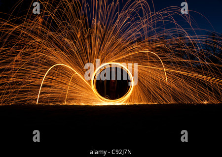 Steel wool spinning, creating gorgeous circular streaks of golden light from burning wire wool inside a whisk attached - Stock Photo
