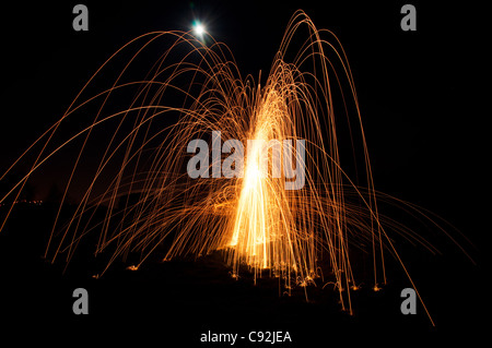 Steel wool spinning. Requires the photographer to set fire to a tuft of steel wool tucked  inside a wire whisk attached - Stock Photo