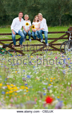 Portrait of smiling family holding sunflowers on fence in wildflower field - Stock Photo