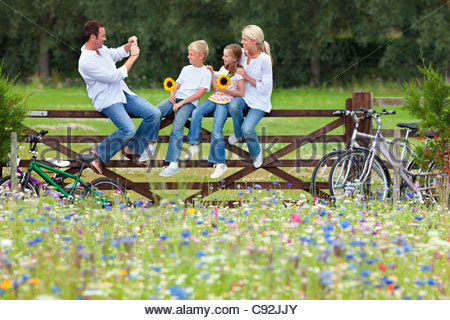 Man taking photograph of family on fence in wildflower field - Stock Photo