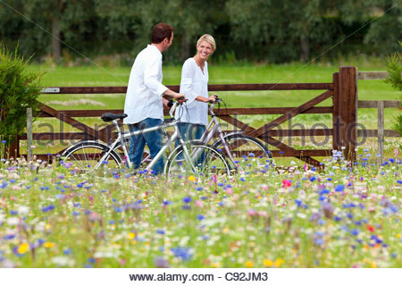 Couple with bicycles walking in wildflower field - Stock Photo