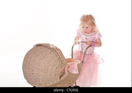little girl dressed in pretty pink dress playing with old baby stroller carriage against white background - Stock Photo