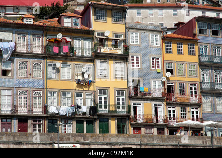 There are historic terraced houses along the riverfront in Oporto along the Douro river which flows through the - Stock Photo