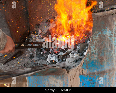 Blacksmith working on an object in the hot coal - Stock Photo