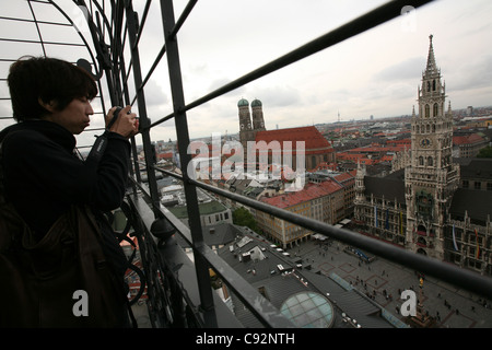 Tourist takes picture of the Marienplatz Square from the tower of the St Peter's Church in Munich, Germany. - Stock Photo