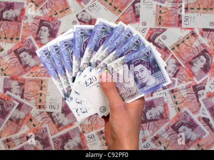 Hand full of new £20 twenty pound notes against background of £50 fifty pound bank notes - Stock Photo