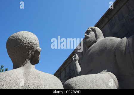 A statue of Saint Mesrop Mashtots founder of the Armenian alphabet stands in front of the Matenadaran Institute - Stock Photo