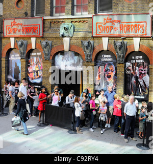 Looking down on group of people waiting in line queuing to buy tickets to enter the London Dungeon visitor attraction - Stock Photo