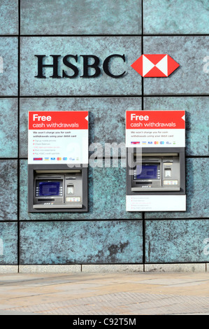 Two HSBC bank ATM cash machines free withdraw cash from a hole in wall of bank premises below bank sign and logo - Stock Photo
