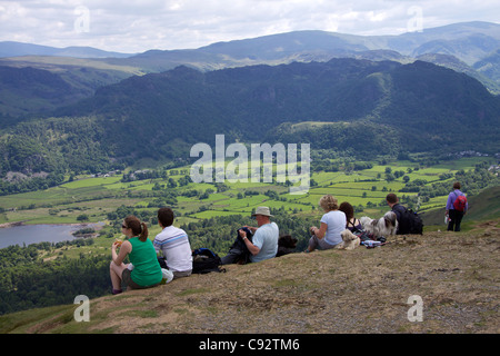The Lake District is a a popular holiday destination famous for its lakes and its mountains or fells . Seven walkers - Stock Photo