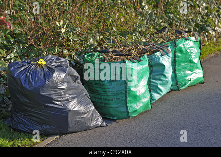 Garden waste and household wasteup on pavement awaiting collection by Wokingham District Council, Berkshire, UK - Stock Photo