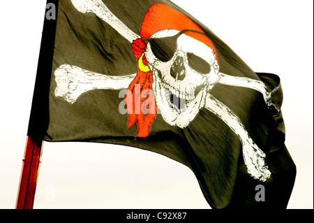 The Jolly Roger skull and cross bones pirate flag - Stock Photo