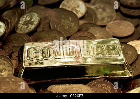 British coins and imitation gold bullion bar in UK seaside resort amusement arcade Penny Falls slot gambling machine - Stock Photo