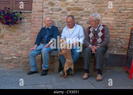 Three older adult Italian men sit on a bench midday petting a dog in Panicale, Italy. - Stock Photo