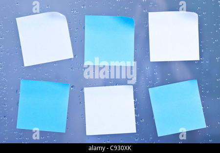 Six sticky notes on a bathroom glass panel with lots of water droplets - Stock Photo