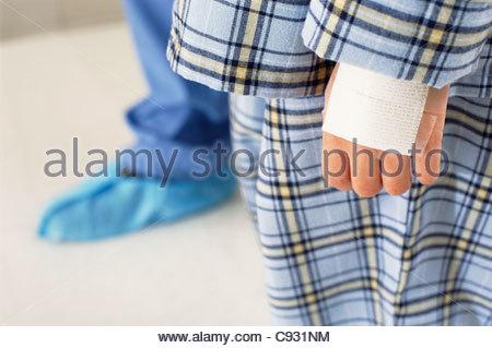 Close up of bandage on hand of boy in pajamas - Stock Photo
