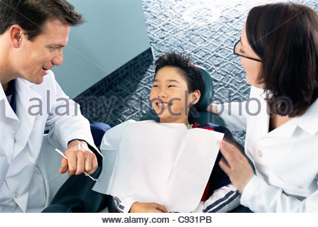 Dentist and dental hygienist talking to smiling boy in dentist chair - Stock Photo