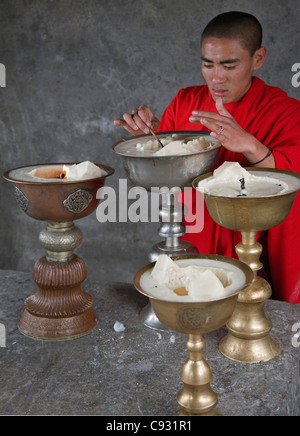 A monk lights butter lamps at Yongla Goemba monastery, one of the holiest shrines in southeast Bhutan. - Stock Photo