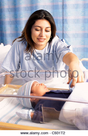 Mother looking down at newborn baby boy in hospital - Stock Photo