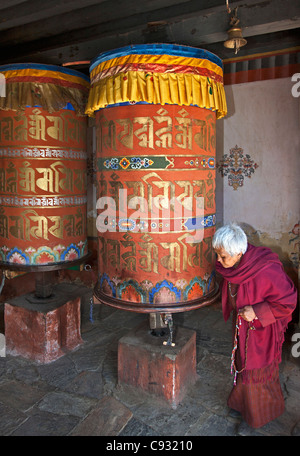 An old woman, turns a large prayer wheel at the Jampay Lhakhang on the outskirts of Jakar in Bumthang Valley. - Stock Photo