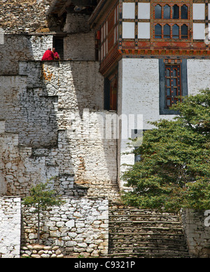 Two red-robed Buddhist monks chat in the sun on stone steps leading to the 17th century Kurjey Lhakhang temple. - Stock Photo