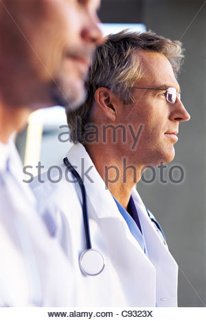 Close up of pensive doctors in lab coats - Stock Photo