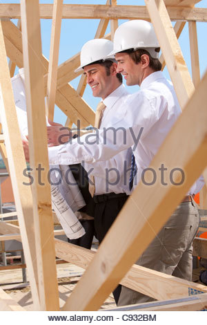 Architects reviewing blueprints at construction site - Stock Photo