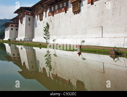 A young monk walks along the outside wall of Punakha Dzong, is the second oldest and largest dzong in Bhutan. - Stock Photo