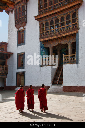 Three monks cross a courtyard in the Punakha Dzong, is the second oldest and largest dzong in Bhutan. - Stock Photo