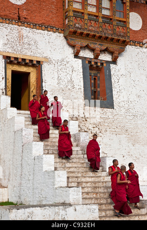 Red robed monks leave the massive Punakha Dzong,  is the second oldest and largest dzong in Bhutan. - Stock Photo