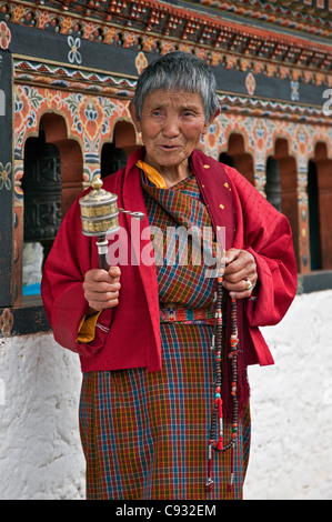 A devout Buddhist woman spins her hand-held prayer wheel at Punakha Dzong, is the second oldest and largest dzong - Stock Photo