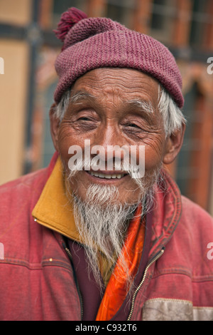 A jovial old monk outside the Changangkha Temple, a fine 15th century temple, on the outskirts of Thimphu. - Stock Photo