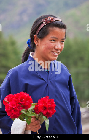 A student with a bunch of red rhododendrons, which she had picked in the Upper Paro Valley. - Stock Photo